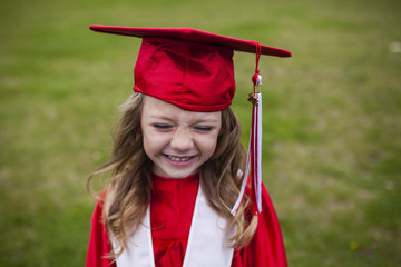 Happy girl in graduation gown on field