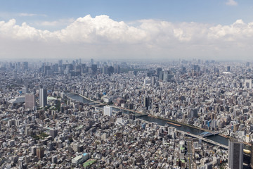 Aerial view of cityscape against cloudy sky on sunny day