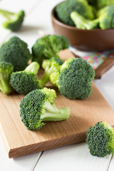 Fresh broccoli scattered on wooden table.