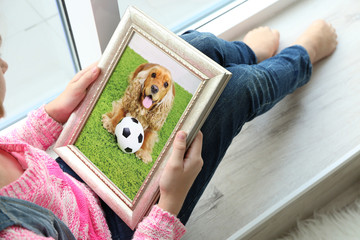Little girl holding photo frame with picture of dog. Happy memories concept.