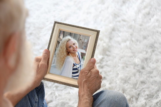 Elderly man holding photo frame with picture of young woman. Happy memories concept.