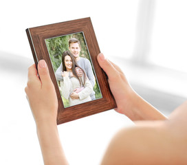 Female hands holding photo frame with picture of young couple. Happy memories concept.