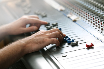 Hands on mixer in a recording studio, close up