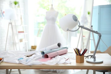 Sewing patterns and cloth on dress designer table