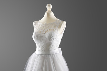 Made-up wedding dress on mannequin against grey background