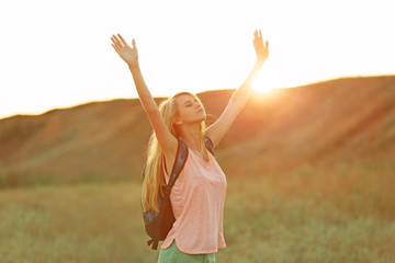 Young woman with raising hands on blue sky background