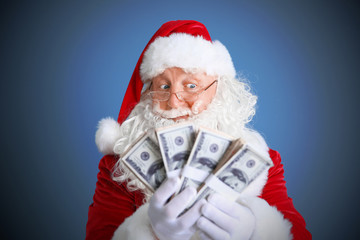 Santa Claus holding money on blue background