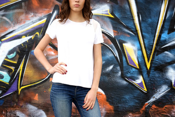 Young woman in blank t-shirt against graffiti wall, closeup