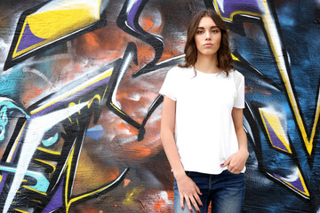 Young woman in blank t-shirt against graffiti wall