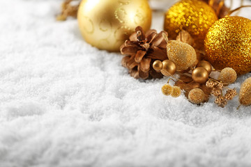 Composition of beautiful Christmas decor and cone on white snow, close up