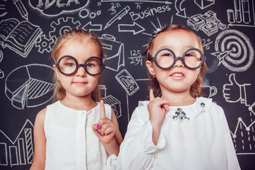 Two little smart girls in glasses lifting finger up on a background of wall with business or school picture