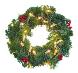 Christmas green wreath with red berries and glowing christmas lights isolated n white background