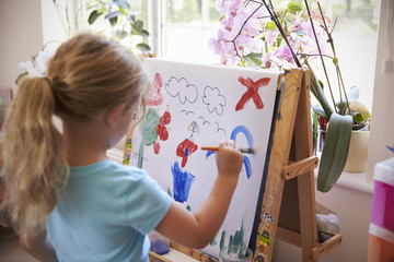 Girl Painting Picture On Easel At Home