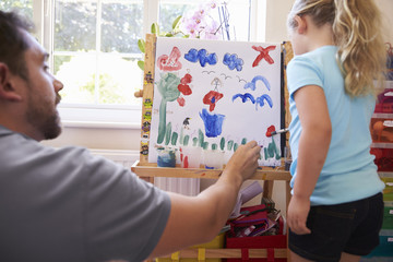 Father Watches Daughter Painting A Picture At Home