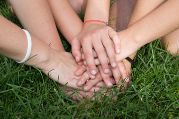 Hands top each other with grass background
