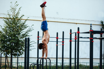 Sportsman at crossfit ground doing push ups as part of training. Sport concept