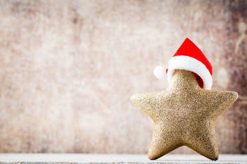 Christmas star with Santa hat. Vintages background.