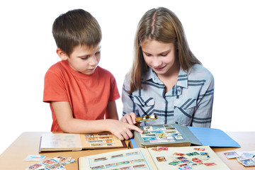 Teen girl and little boy with magnifier looking his stamp collec