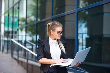 Business girl or woman in glasses sits with the laptop outdoors