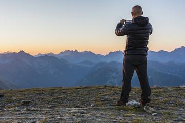 Boy doing photo peaks at sunrise.