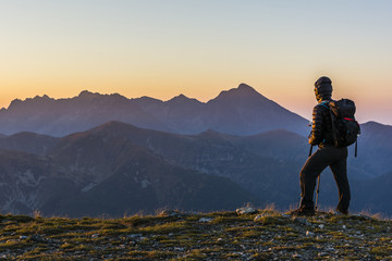 Hiker with backpack and trekking poles at sunrise.