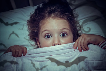 cute little girl with scary eyes under the blanket in her bed