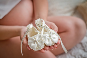Bootees for the newborn girl in the pregnant woman's hands