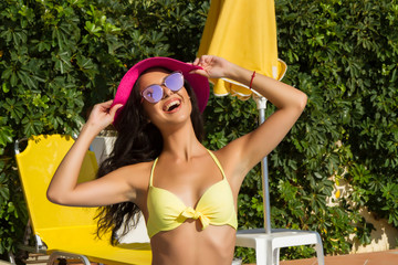 Beautiful brunette with bikini, pink hat and sunglasses at pools