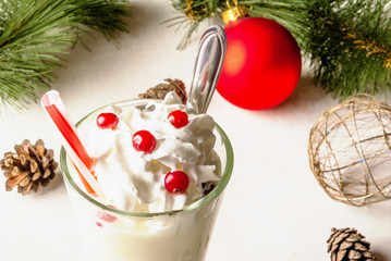 Christmas cranberry smoothie and yogurt with whipped cream. Against the background of the Christmas tree branches and Christmas decorations. Close view