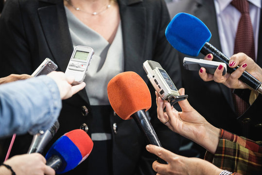 Female politician surrounded with journalists