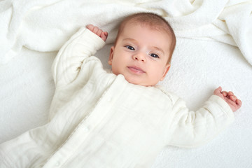 baby portait lie on white towel in bed