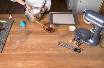Cream mixing on kitchen table with kitchenware
