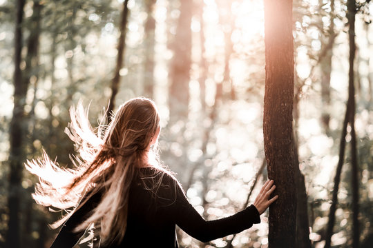 Woman Standing in Sun with Wind Blowing Long Hair
