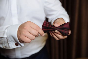 Wedding accessories. Brown Bow tie in the hands of the groom