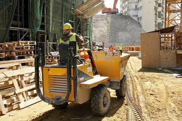 Little construction dumper carrier is at building site.