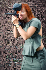 Girl takes aim from a paintball gun on a background of camouflage nets