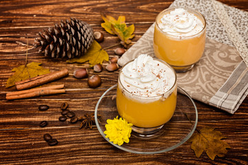 Pumpkin smoothie, spice latte with whipped  cream on the rustic wooden background.  selective focus