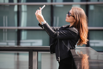 Young beautiful woman taking a selfie in the city