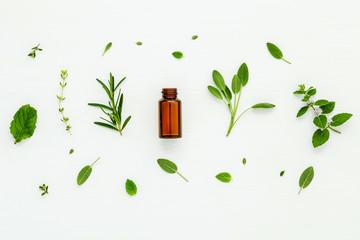 Bottle of essential oil with fresh herbal sage, rosemary, lemon