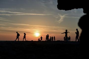 sahil kenarında günbatımı izleyen insanlar