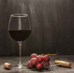 Red wine, grapes, corkscrew, cork. Low-key photo