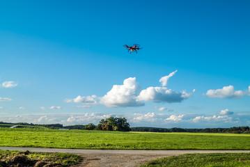 Quadrocopter über Landstraße im Landeanflug