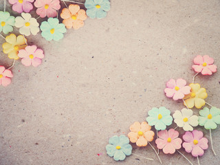 Colorful pastel artificial flower on recycled paper background,