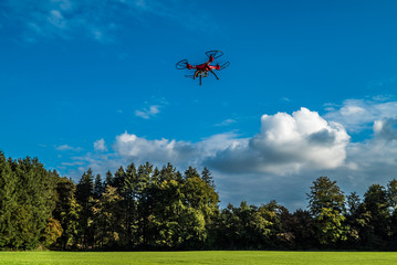Rasanter Flug einer roten Drohne unter weiß-blauem Himmel