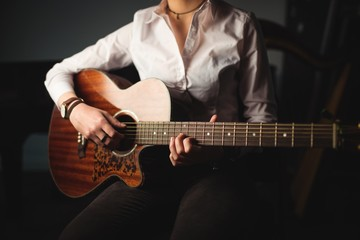 Woman playing a guitar in music school
