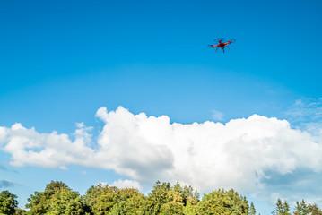 Roter Quadrokopter unter blauem Himmel zieht seine Kreise