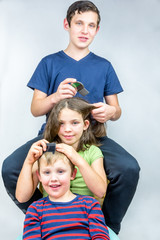 Three children who comb each others head. Efficient head lice treatment, studio portrait shot.