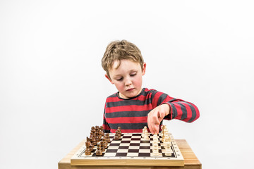 Boy paying chess with himself, portrait studio shot. Landscape format.