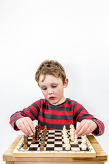 Boy playing chess with himself, portrait studio shot.