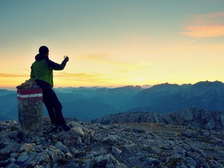 Hiker takes selfie photo. Man  sit on Austria Germany border stone on Alpine mountain.
